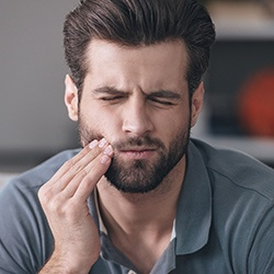 Man with teeth pain holding cheek