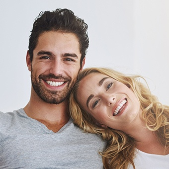 Couple leaning against each other smiling