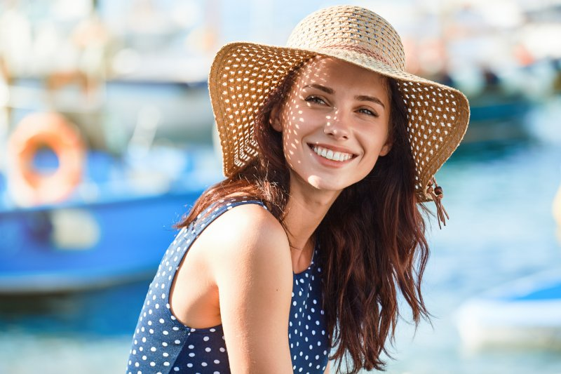 girl in straw hat smiling in the sunshine after cosmetic treatment